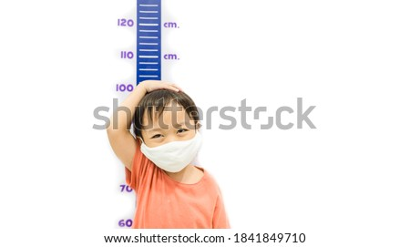 Height measure kid boy wearing mask.Kid measures the growth isolated white wall.3.6 years old boy kid standing using hand measuring his height.Growth hormones, child development, Calcium supplements.