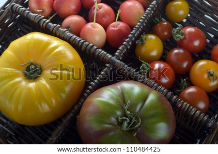 Heirloom and cherry tomatoes and crab apples in woven wooden basket