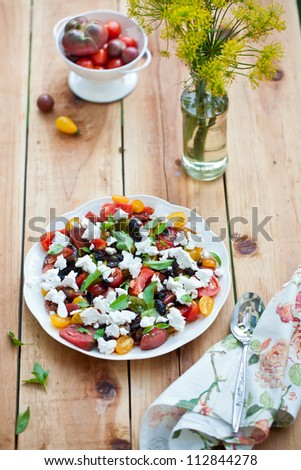 Heirloom tomatoes salad with cheese on wooden surface
