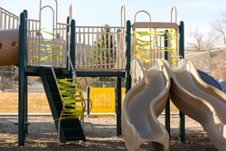 Helena, Montana - March 30, 2020: Playground closed with yellow caution tape wrapped around slide & stairs to prevent spread of novel Coronavirus to children. Health and safety due to Covid-19.