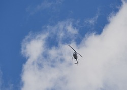 Helicopter against a blue sky with clouds.