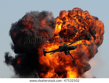 helicopter against giant fireball with smoke and flames