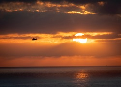 helicopter banking left away from the sun during a cloudy sunset over the pacific ocean