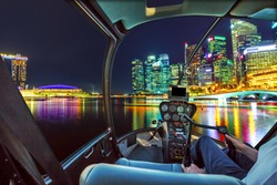 Helicopter cabin interior flying on Panorama of Singapore buildings and skyscrapers of downtown reflected in the sea. Singapore scenic flight by night.