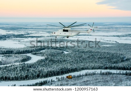 Helicopter carries cargo over the taiga #1200957163
