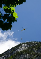 helicopter carrying a small cargo load above mounts in Lauterbrunnen Valley. Switzerland