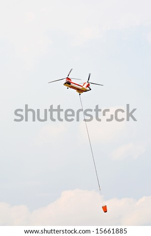 helicopter carrying water drop bucket, heavy twin-rotor aircraft fighting forest fire in US, motion blur on rotors