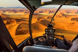 Helicopter cockpit flies in Dead Valley, Sossusvlei desert in Namib Naukluft National Park, Namibia, with pilot arm and control board inside the cabin.