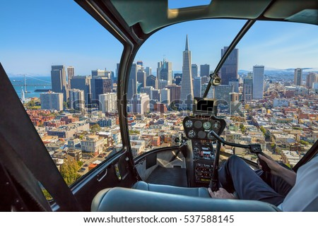 Helicopter cockpit flies in San Francisco Financial District Downtown, California, United States, with pilot arm and control board inside the cabin in a sunny day.