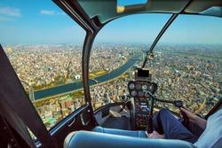 Helicopter cockpit inside the cabin flying on Tokyo city skyline, Sumida River Bridges and Asakusa area. Daytime. Tokyo, Japan.