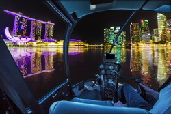 Helicopter cockpit interior flying on Panorama of Singapore buildings and skyscrapers of downtown reflected in the sea. Singapore skyline by night flight and nocturnal scene of marina bay waterfront