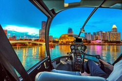 Helicopter cockpit interior flying on Skyline of Singapore in marina bay with cruise boats in the harbor at blue hour. Night scene waterfront in Singapore bay.