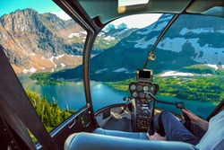 Helicopter cockpit with pilot arm and control console inside the cabin flight over Spectacular aerial view of Hidden Lake Overlook in Glacier National Park, Montana, United States.