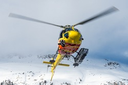 helicopter departing on a mission to drop some heli skiers on top of a mountain. The basket on the side is loaded with skies