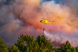Helicopter dumping water with bambi-bucket over the fire