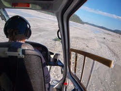 Helicopter flight over a rugged wilderness landscape in new zealand, seen from the cockpit