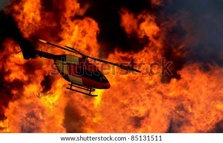 Helicopter flying by a bushfire - stock photo