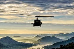 helicopter flying on hill and river.