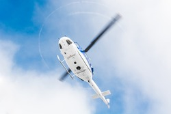 Helicopter flying under sky covered with clouds
