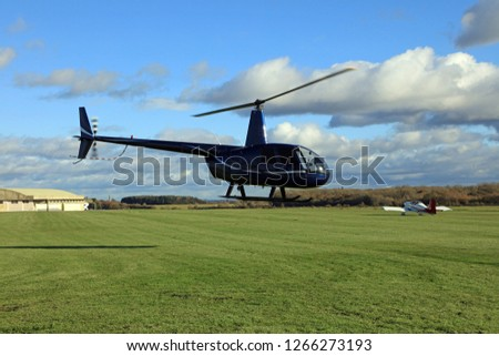 Helicopter Hovering Over A Grass Airfield.