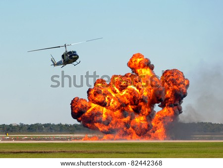 Helicopter hoving over giant ground explosion and fire