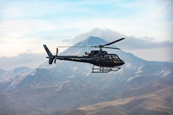 Helicopter in flight. Black Helicopter is flying between mountains peak, winter time. A beautiful Caucasian mountain in the background scene. Luxury Lifestyle, Vacation tour on helicopter