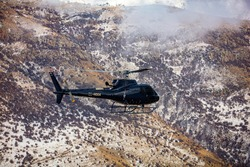 Helicopter in flight. Black Helicopter is flying between mountains peak, winter time. Luxury Lifestyle. Vacation tour on Helicopter
