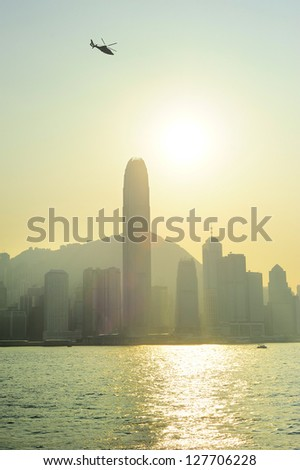Helicopter in Hong Kong sky at sunset