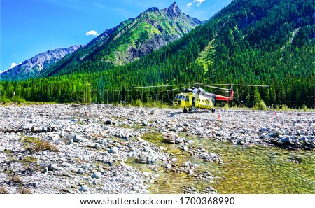 Helicopter landing at mountain river valley. Mountain valley river helicopter landing. Helicopter landing in mountain valley
