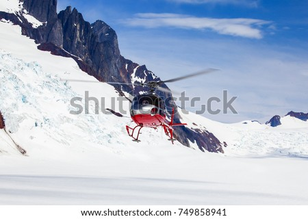 helicopter landing on a remote mountain glacier