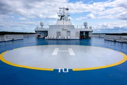 Helicopter landing site helipad helideck of a big ship boat tanker with captain's bridge in the background - concept passenger transport sea travel copter flight maritime aviation nautical nautics