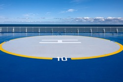 Helicopter landing site helipad helideck of a big ship boat tanker with white railing, ocean water, skyline and blue sky in background - concept transport sea travel copter flight maritime aviation