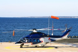 Helicopter on the platform near the sea.