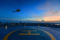 Helicopter parking landing on the roof of a skyscraper with cityscape view at sunset