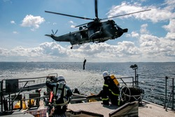 Helicopter rescue mission in difficult stormy weather at sea. Military helicopter and ship in sea. Army helicopter and ship training in Baltic sea. Rescue mission in sea with ship and helicopter.