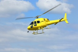 Helicopter rescue, Yellow helicopter in the air while flying on blue sky. All logos and text removed.