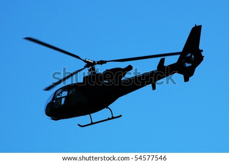 Helicopter silhouette opposite blue sky - stock photo