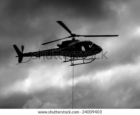 Helicopter Silhouette with Sling Load - stock photo