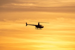 Helicopter silhouette with vibrant sunset sky with clouds