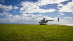helicopter standing on the gound on green grass blue sky summer