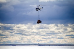 Helicopter transport cargo from vessel to coast, on horizon visible beacon. Suspension drums, sling load operation. Flying over sea in cloudy weather