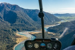 Helicopter window view of mountain valley with river. Luxury tourism, travel experience background