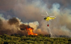 Helicopter with bambi bucket dumping water over the flames