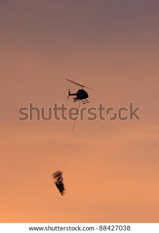 Helicopter with sling load flying into the sunset.