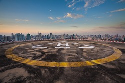 Helipad on the roof of a skyscraper with cityscape view