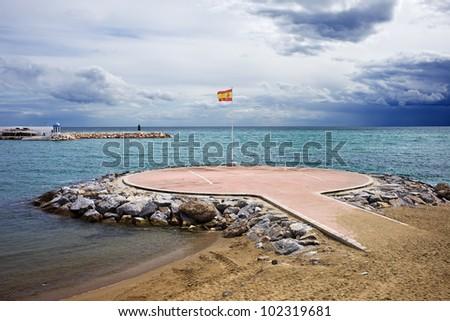Heliport on the Mediterranean Sea with Spanish flag in Marbella, Costa del Sol, Malaga Province, Spain