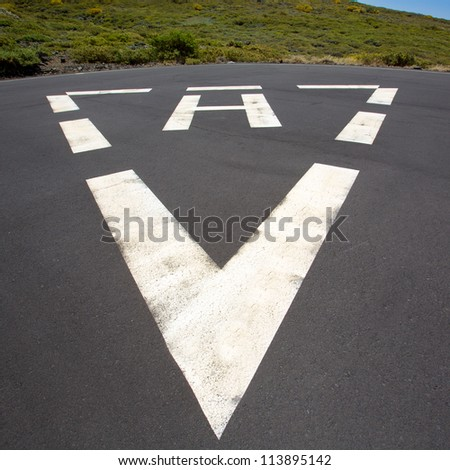 heliport triangle white soil painted sign in pavement - stock photo