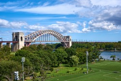 Hell Gate Bridge, with the fields of Wards Island and Randalls Island Park in the foreground. Hell Gate Bridge is a metal arch railroad bridge, spanning the East River, built in 1916.