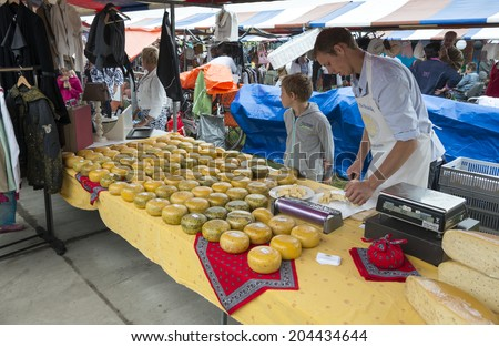 HELLEVOETSLUIS,NETHERLANDS-JULY 12, 2014: Farmer selling dutch cheese at the anual farmers market in Hellvoetsluis on July12,this market is only once a year and selling clothes and fresh food