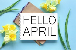 Hello April . text on white notepad paper on blue background. near notepad with yellow flowers and green leaves